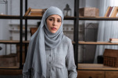 sad muslim woman in hijab looking at camera in living room, domestic violence concept