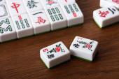KYIV, UKRAINE - JANUARY 30, 2019: selective focus of mahjong game tiles on wooden table