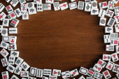 KYIV, UKRAINE - JANUÁR 30, 2019: keret fehér mahjong játék csempe a fa asztalra, felső nézet