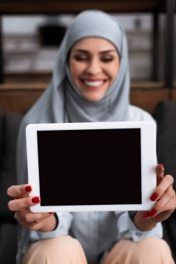 Selective focus of positive arabian woman in hijab holding digital tablet with blank screen in living room stock vector