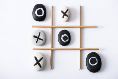 Top view of tic tac toe game with grid made of paper tubes, and pebbles marked with naughts and crosses on white surface stock vector