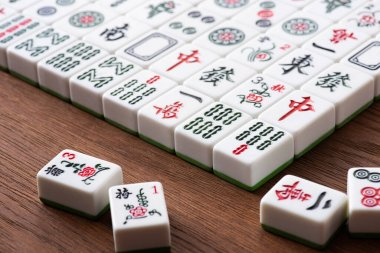 KYIV, UKRAINE - JANUARY 30, 2019: selective focus of field of mahjong game tiles with signs and characters on wooden table stock vector