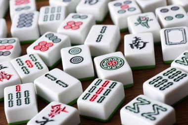 KYIV, UKRAINE - JANUARY 30, 2019: selective focus of white mahjong game tiles with signs and characters on wooden surface stock vector