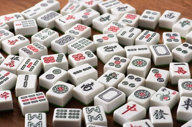 KYIV, UKRAINE - JANUARY 30, 2019: selective focus of white mahjong game tiles with signs and characters on wooden table stock vector