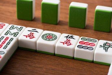 KYIV, UKRAINE - JANUARY 30, 2019: selective focus of mahjong game tiles rows on wooden table stock vector
