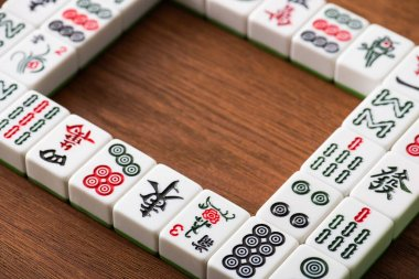 KYIV, UKRAINE - JANUARY 30, 2019: selective focus of square frame and rows of mahjong game tiles on wooden table stock vector