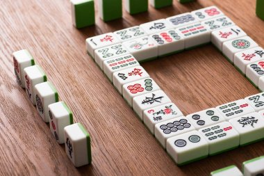 KYIV, UKRAINE - JANUARY 30, 2019: square frame and rows of mahjong game tiles on wooden table stock vector