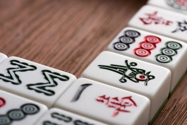 KYIV, UKRAINE - JANUARY 30, 2019: close up view of white mahjong game tiles with signs and characters on wooden table stock vector