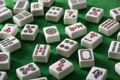 KYIV, UKRAINE - 2019. június 30.: a fehér mahjong játéklapok szelektív fókusza zöld velúr felületen jelekkel és szimbólumokkal