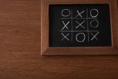 top view of tic tac toe game on blackboard with chalk grid, naughts and crosses on wooden surface