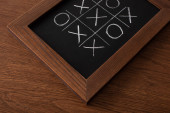 Photo tic tac toe game on blackboard with chalk grid, naughts and crosses on wooden surface