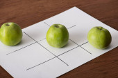 Photo tic tac toe game on white paper with row of three green apples on wooden surface