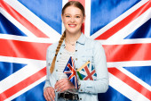 Fotografie smiling pretty girl with braid holding book on uk flag background