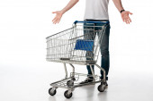 cropped view of man gesturing while standing near empty shopping cart on white