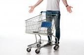 oříznutý pohled na muže gestikulujícího při stání poblíž prázdného nákupního vozíku na bílém