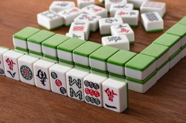 KYIV, UKRAINE - JANUARY 30, 2019: selective focus of mahjong game tiles with signs and symbols on wooden surface stock vector