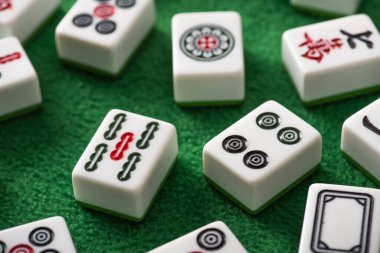 KYIV, UKRAINE - JANUARY 30, 2019: selective focus of white mahjong game tiles with signs and symbols on green velour surface stock vector