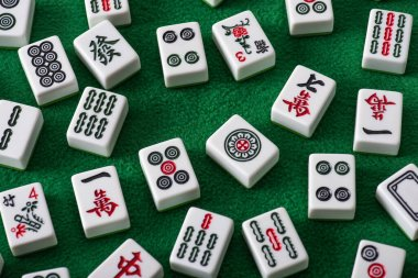 KYIV, UKRAINE - JANUARY 30, 2019: top view of white mahjong game tiles with signs and characters on green velour surface stock vector
