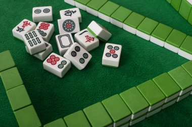 KYIV, UKRAINE - JANUARY 30, 2019: rows and stack of mahjong game tiles on green velour surface stock vector