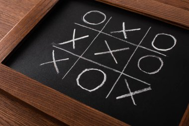 Tic tac toe game on blackboard with chalk grid, naughts and crosses on wooden surface stock vector