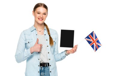 Smiling pretty girl with braid holding digital tablet with blank screen and uk flag while showing thumb up isolated on white stock vector