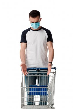 Man in medical mask gesturing while looking at empty shopping cart isolated on white stock vector
