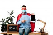 férfi orvosi maszk és szuperhős köpeny ujjal mutat a digitális tabletta üres képernyő közelében kréta tábla marad otthon betű elszigetelt fehér