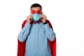 férfi szuperhős jelmezben megérinti orvosi maszk elszigetelt fehér