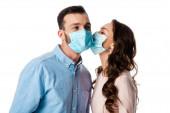 Frau küsst Mann in medizinischer Maske isoliert auf weiß
