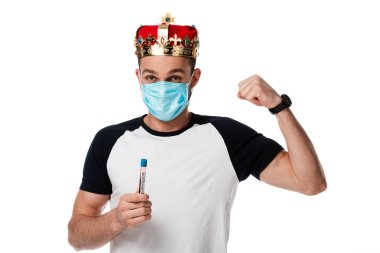 man in medical mask and crown holding test tube with coronavirus blood sample and showing fist isolated on white