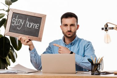 bearded freelancer pointing with finger at chalk board with stay home lettering isolated on white