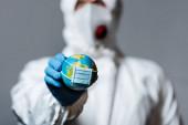 Selektiver Fokus des Mannes im Schutzanzug mit kleinem Globus in medizinischer Maske isoliert auf grau