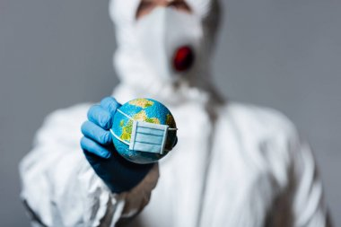 Selective focus of man in hazmat suit holding small globe in medical mask isolated on grey stock vector