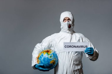 Man in personal protective equipment holding globe and paper with coronavirus lettering isolated on grey stock vector