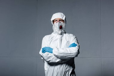 Man in personal protective equipment standing with crossed arms on grey stock vector