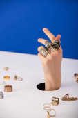 selective focus of woman with bracelet on hand near golden rings isolated on blue