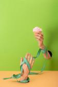 levágott kilátás nő mérőszalaggal a kezén gazdaság cupcake zöld és narancssárga