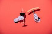 oříznutý pohled na ženu v rukavicích, držící sklo s červeným vínem a vidličkou s klobásou na červené