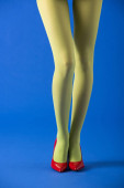 cropped view of model in green tights standing on blue