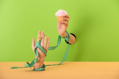 Cropped view of woman with measuring tape on hands holding tasty cupcake on green and orange stock vector