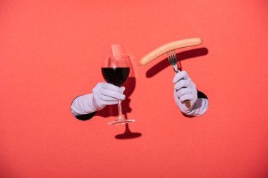 Cropped view of woman in gloves holding glass with red wine and fork with sausage on red stock vector