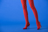 cropped view of woman in fishnet tights and red heels posing on blue