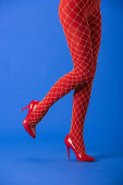 cropped view of woman in red fishnet tights and heels posing on blue