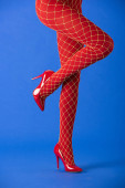 cropped view of stylish woman in fishnet tights and red heels posing on blue