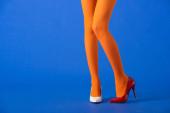 ořezaný pohled na trendy model v oranžových punčocháčích, bílé a červené podpatky pózující na modré