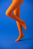 cropped view of woman in bright orange tights posing on blue