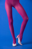 cropped view of woman in bright purple tights and shoes standing on blue
