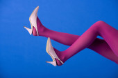 cropped view of model in bright purple tights and heels posing on blue