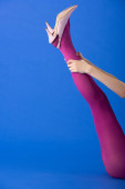 Photo cropped view of model touching bright purple tights on blue