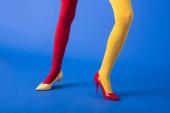 oříznutý pohled na ženu ve žlutých a červených punčocháčích a podpatcích pózujících na modré